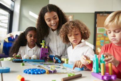 female-teacher-sitting-at-table-in-play-room-with-three-kindergartne-children-constructing.jpg