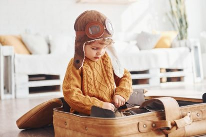 little-boys-in-retro-pilot-costume-have-fun-and-sitting-in-suitcase-indoors-at-daytime.jpg